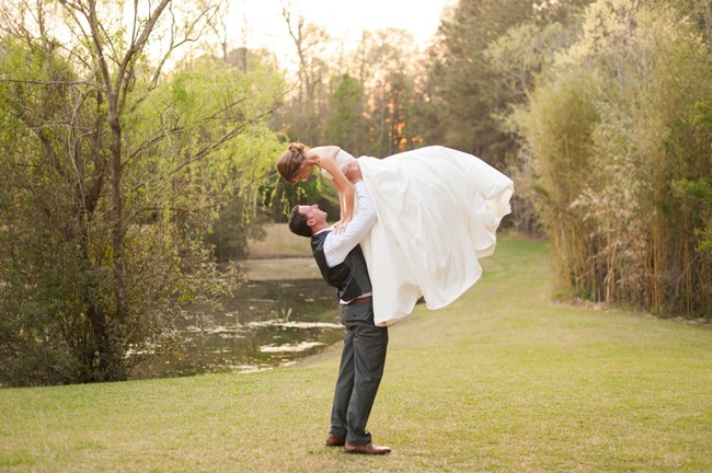 groom-lifting-bride-over-her-head-in-field