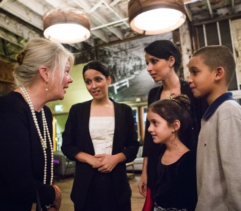 Karen Olsen talks with twin sisters, Sarah, left, and Rebecca, along with Sarah's daughter Sarah, 7, and Rebecca's son, Emmanuel, 9, as they thank her for the evening donated to Mary's Place families at Sodo Park on Saturday. (Lindsey Wasson / The Seattle Times)
